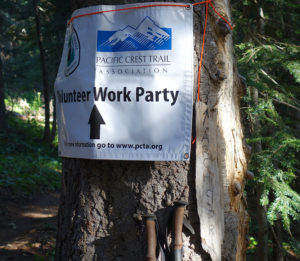 PCT work party sign pinned to a tree